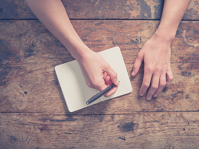 Woman writing in notepad at wooden table